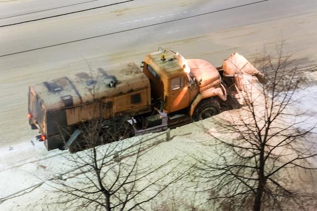 Les souffleuses à neige desservent les routes de la ville la nuit. meunier lourd ou camion fresia nettoyant la route de la neige pendant le blizzard ou la tempête de neige en hiver.