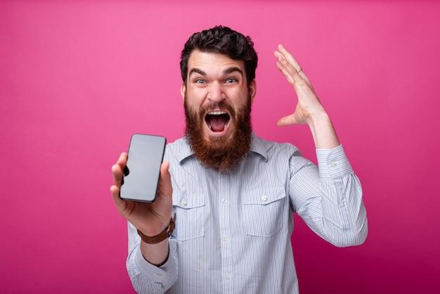 Soufflez votre concept de l'esprit. jeune homme barbu montrant l'écran vide du smartphone, gesticulant avec sa main près de sa tête.
