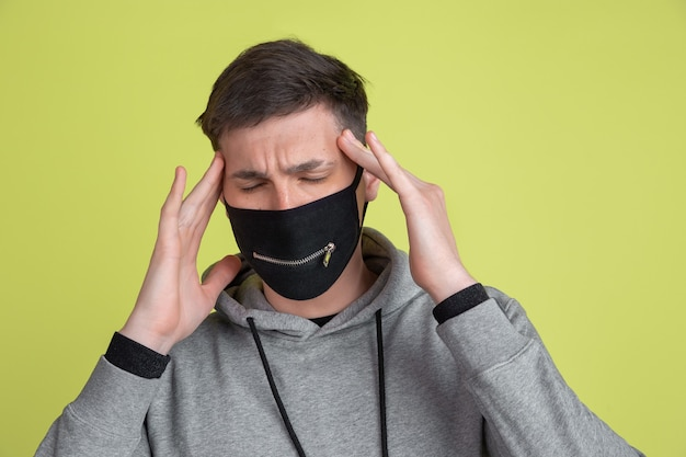 Souffrance de maux de tête. portrait d'un homme de race blanche isolé sur un mur de studio jaune. modèle masculin en masque facial noir.