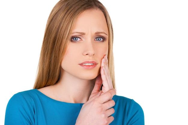 Souffrant de maux de dents. jeune femme frustrée touchant sa joue et regardant la caméra en se tenant debout isolé sur blanc