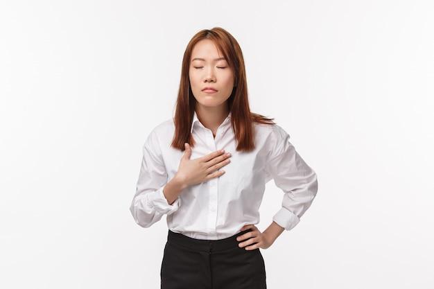 Soulagé et relaxant femme asiatique essayant de respirer et d'être calme, toucher la respiration thoracique paisible, fermer les yeux, soulager le stress, debout mur blanc se prépare pour la présentation