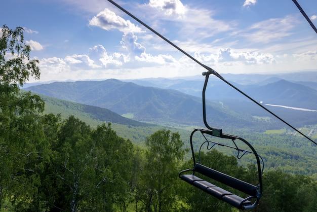 Soulevez le fond des montagnes et des collines verdoyantes par une journée d'été ensoleillée. banc vide de remontées mécaniques, le tourisme a fermé la quarantaine.