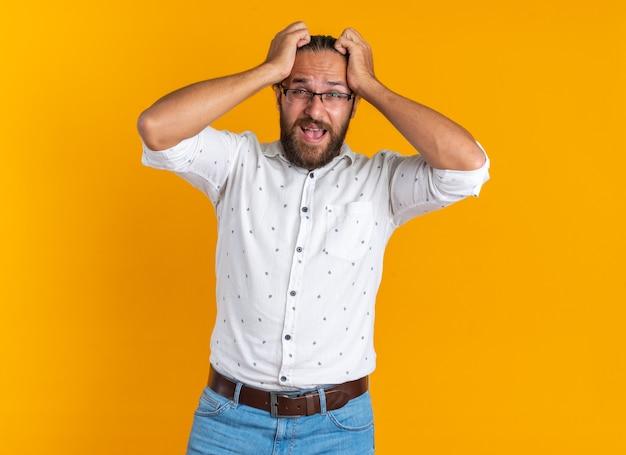 A souligné un bel homme adulte portant des lunettes en gardant les mains sur la tête en criant