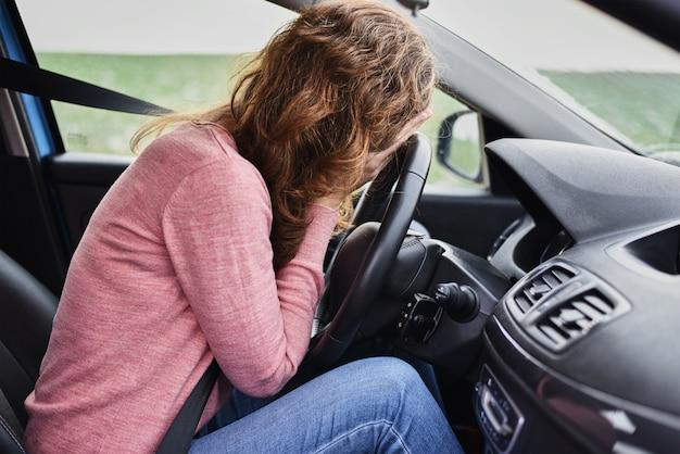 A souligné la femme couvrant le visage avec les mains dans la voiture. concept de panique du conducteur