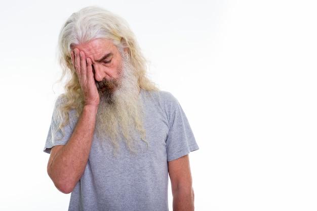 A souligné homme barbu senior ayant des maux de tête
