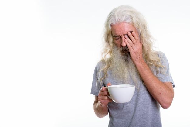 A souligné homme barbu senior couvrant le visage tout en tenant la tasse