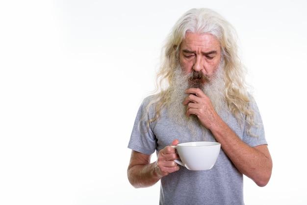 A souligné l'homme barbu senior pensant tout en tenant une tasse blanche