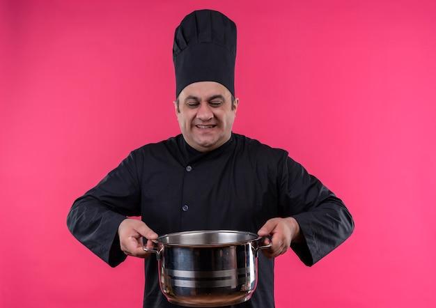 Souligne les hommes d'âge moyen cuisinier en uniforme de chef tenant une casserole lourde
