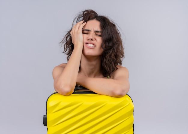 A souligné jeune femme belle voyageur tenant valise et mettre la main sur le visage sur un mur blanc isolé