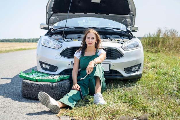 A souligné la jeune femme regardant le moteur de sa voiture. problèmes de voyage sur la route. la voiture a besoin d'une réparation.