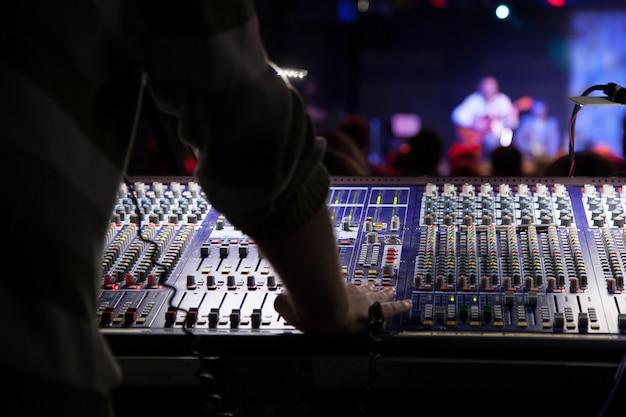 Soundman travaillant sur la console de mixage. les mains sur les curseurs.