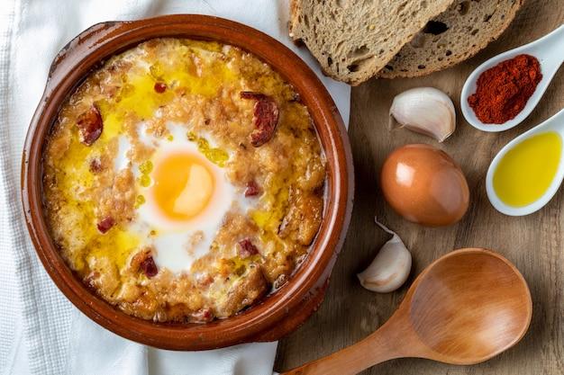 Soupe à l'ail et au pain en pot d'argile et ses principaux ingrédients