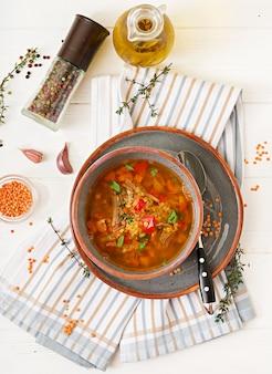 Soupe appétissante avec lentilles rouges, viande, paprika rouge et thym parfumé. mise à plat. vue de dessus