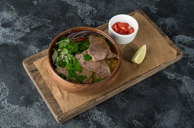 Soupe asiatique dans une assiette en bois, soupe pho bo, mise à plat