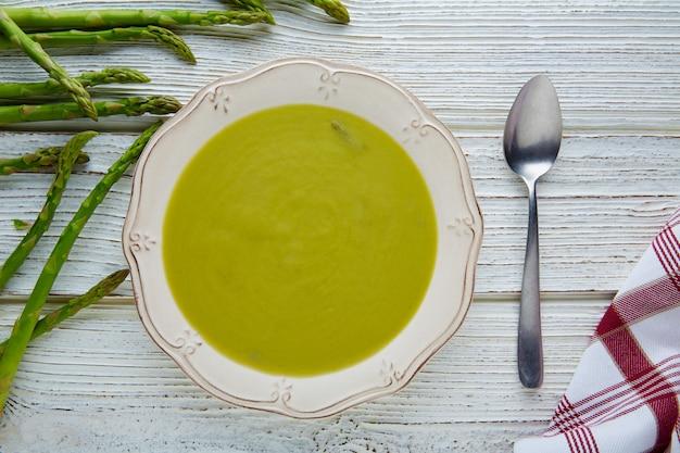 Soupe d'asperges vert crème sur une table en bois blanc