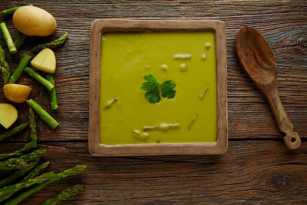 Soupe d'asperges vert crème sur une table en bois vieilli