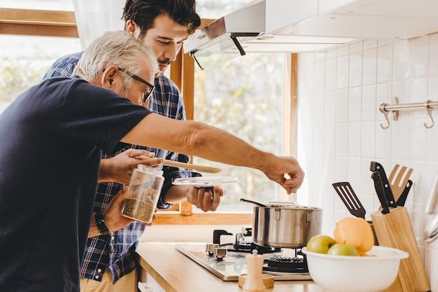 Soupe d'assaisonnement aux personnes âgées avec des ingrédients naturels cuisinant avec un jeune homme pour rester à la maison en famille.