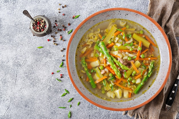 Soupe au bœuf, asperges, pois verts, carottes et céleri. vue de dessus.