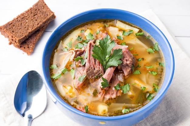 Soupe au chou traditionnelle russe avec de la viande et des herbes fraîches sur une table lumineuse.
