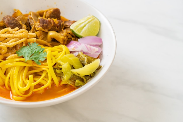 Soupe au curry de nouilles du nord de la thaïlande et porc braisé - style cuisine thaï