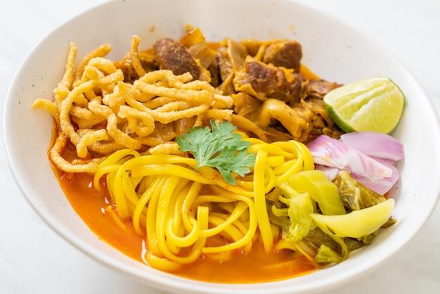Soupe au curry de nouilles du nord de la thaïlande avec porc braisé - style cuisine thaïlandaise