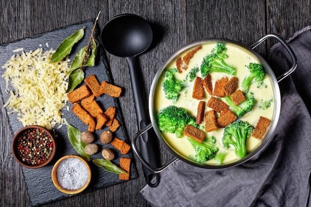 Soupe au fromage à la crème avec croûtons de brocoli et de seigle dans une casserole sur une table en bois sombre avec cuillère et ingrédients, vue horizontale d'en haut, mise à plat