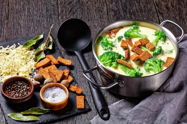 Soupe au fromage à la crème avec croûtons de brocoli et de seigle dans une casserole sur une table en bois sombre avec cuillère et ingrédients, vue horizontale d'en haut