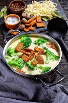 Soupe au fromage à la crème avec croûtons de brocoli et de seigle dans une casserole sur une table en bois sombre avec cuillère et ingrédients, vue verticale d'en haut