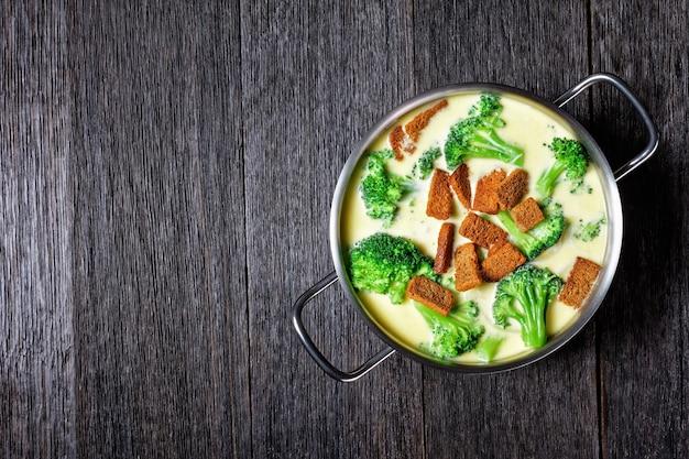 Soupe au fromage à la crème avec croûtons de brocoli et de seigle dans une casserole sur une table en bois sombre, vue horizontale d'en haut, mise à plat, espace libre