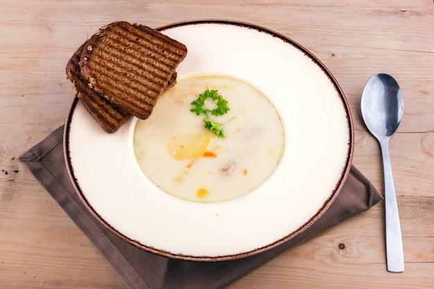 Soupe au fromage dans une assiette blanche avec du pain grillé