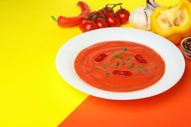 Soupe au gaspacho et ingrédients sur fond bicolore