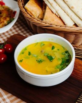 Soupe au poulet, carottes, pommes de terre, verts, vue latérale