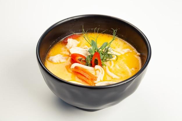 Soupe au poulet et lait de coco dans un karelian noir.