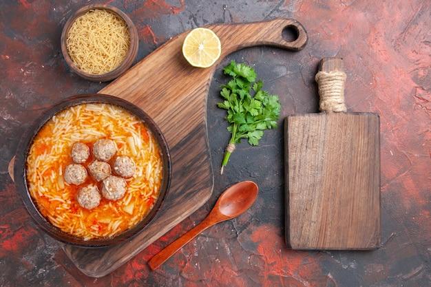 Soupe au poulet avec nouilles à bord et pâtes non cuites, verts de citron et planche à découper sur fond sombre