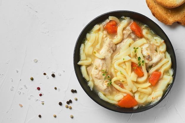 Soupe au poulet et nouilles maison avec des légumes et des épices dans un bol, vue du dessus, fond de béton blanc.