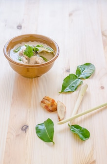 Soupe au poulet thaï au lait de coco (tom kha gai) sur fond en bois, cuisine thaïlandaise.