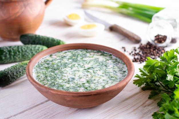 Soupe au yaourt froide d'été okroshka sur une table en bois blanc. tarateur de légumes de radis et de concombre de russie décoré d'oignon vert et d'aneth.