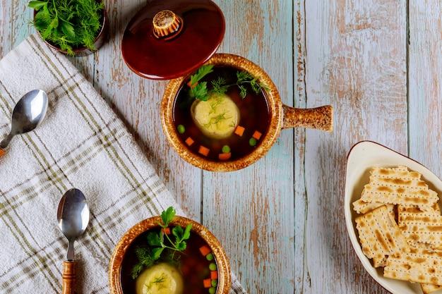 Soupe aux boules de pain azyme dans des bols en céramique avec couvercle.