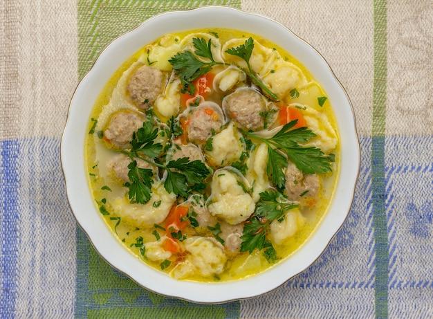 Soupe aux boulettes de viande et boulettes sur une serviette en lin close up top view