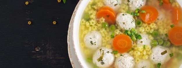 Soupe aux boulettes de viande italienne et pâtes stelline dans un bol sur le tableau noir
