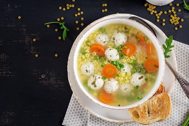 Soupe aux boulettes de viande italienne et pâtes stelline dans un bol sur le tableau noir.