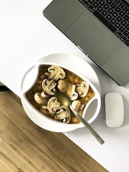 Soupe aux champignons et aux haricots blancs servie sur la table blanche près d'un ordinateur portable et d'une souris