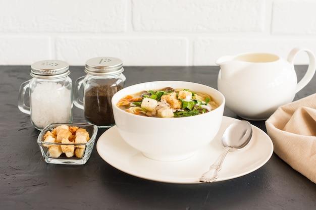 Soupe aux champignons blancs avec persil, crème et croûtons dans une assiette creuse sur fond noir en face d'un mur de briques blanches.