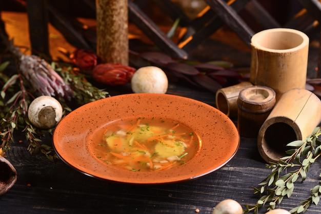 Soupe aux champignons et carottes. sur une table en bois noire avec décor