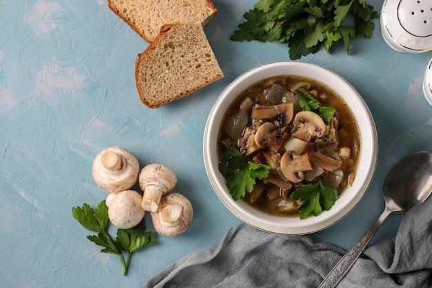 Soupe aux champignons de champignons et lentilles dans une assiette blanche sur fond bleu clair, vue de dessus, espace de copie