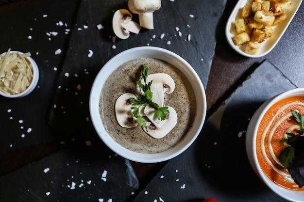 Soupe aux champignons décorée de persil fromage sel vue de dessus