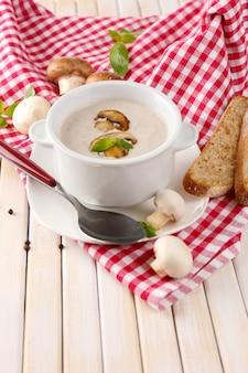 Soupe aux champignons en pot blanc, sur serviette, sur table en bois