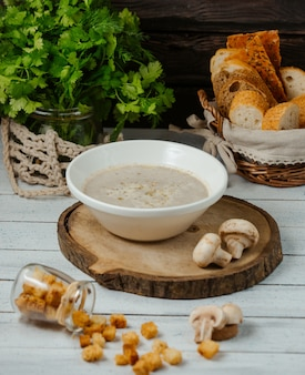 Soupe aux champignons servie avec du pain farci sur une planche en bois