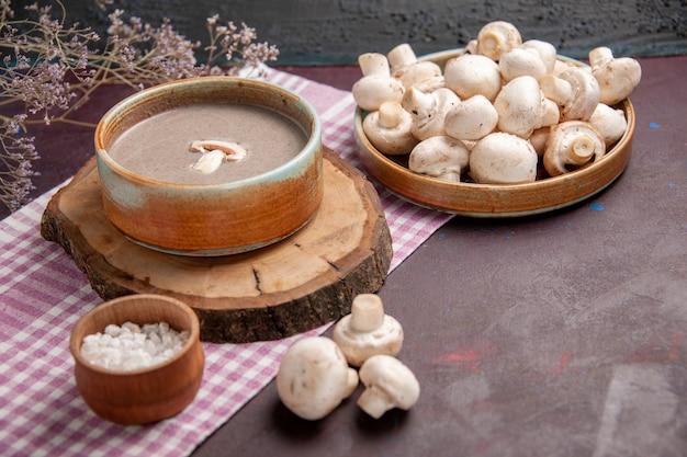 Soupe aux champignons vue de face avec des champignons frais sur l'espace sombre