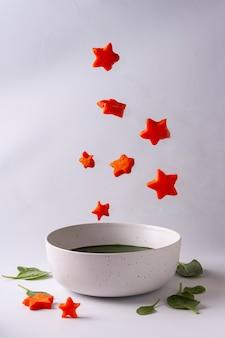 Soupe aux épinards dans un bol et aux étoiles volantes de carottes concept d'aliments sains